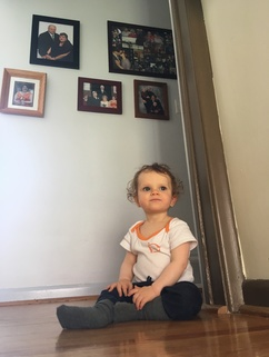 Our daughter in front of family portraits