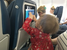 Our daughter trying her luck on the in-flight entertainment system
